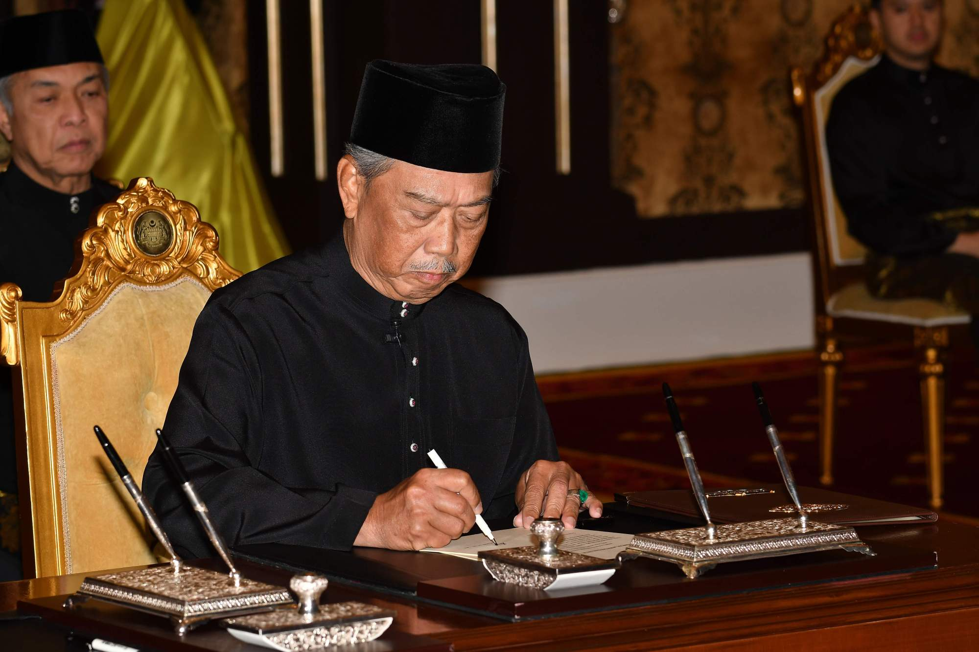 Malaysian Prime Minister Muhyiddin Yassin signs documents after taking the oath as the country's new leader at the National Palace in Kuala Lumpur on Sunday. | AFP-JIJI