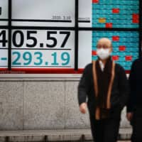 Mask-wearing pedestrians walk past a quotation board displaying the share price index of the Tokyo Stock Exchange on Tuesday. | AFP-JIJI