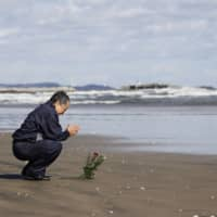 A man prays toward the sea to mourn victims of the March 11, 2011, earthquake and tsunami disaster in Iwaki, Fukushima  Prefecture, on Wednesday, the nine-year anniversary of the disasters. | KYODO