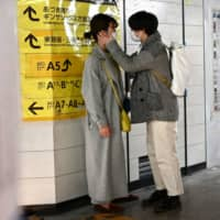 A couple wearing face masks, amid concerns over the COVID-19 coronavirus, chat at a train station in Tokyo on Sunday. | AFP-JIJI