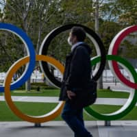 A man wearing a face mask walks in front of the Olympic Rings in Tokyo on March 11. | AFP-JIJI
