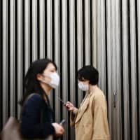 People wearing face masks amid concerns of the COVID-19 coronavirus walk on a street in Tokyo's Yurakucho area Wednesday. | AFP-JIJI