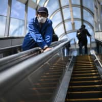 A worker wearing a face mask cleans an escalator at Sendai Station in the city on Saturday amid the coronavirus pandemic. | AFP-JIJI