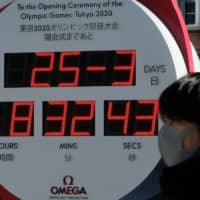 A man walks past an electronic 2020 Tokyo Olympic Games countdown clock showing today's date instead of the countdown days outside Tokyo Station in the Japanese capital on Wednesday. | REUTERS
