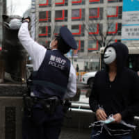 A police officer removes a face mask placed over the statue of famous Japanese dog Hachiko, next to a volunteer distributing masks, amid an outbreak of the COVID-19 virus, at Tokyo's Shibuya Station on Sunday. | REUTERS