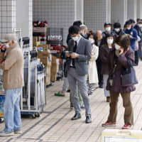 People wearing protective face masks following an outbreak of the new coronavirus line up as they wait for the opening of a drugstore in Tokyo on Friday. | KYODO