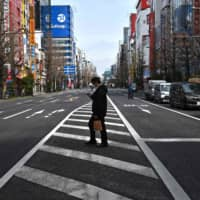 A man wearing a face mask, amid concerns of the COVID-19 coronavirus, crosses a street in Tokyo's Akihabara district on Monday. | AFP-JIJI