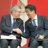 International Olympic Committee chief Thomas Bach and Prime Minister Shinzo Abe shake hands in Tokyo on July 24, 2019, during an event marking the start of the one-year countdown to the opening of the 2020 Tokyo Olympics. | KYODO