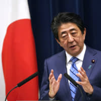 Prime Minister Shinzo Abe explains the government's steps to deal with the coronavirus outbreak during a nationally televised news conference on Saturday in Tokyo. | AP