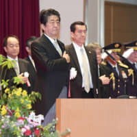 Prime Minister Shinzo Abe attends a graduation ceremony at the National Defense Academy in Yokosuka, Kanagawa Prefecture, on Sunday. | POOL / VIA KYODO