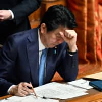 Prime Minister Shinzo Abe rests his head on his fist as he attends an Upper House plenary session at the Diet in Tokyo on Friday. | AFP-JIJI