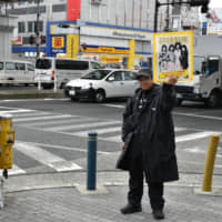 Teruo Irishima holds up a poster promoting the Queen edition of The Big Issue Japan magazine in Osaka on Jan. 28. | KYODO