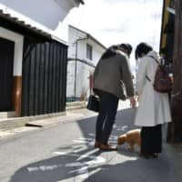 Visitors walk a dog in an alley in Yuasa, Wakayama Prefecture, on Feb. 18. The town is famous for its concentration of traditional soy sauce factories. | KYODO