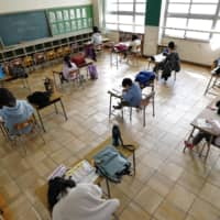 Students sit away from each other as they study at an elementary school in Nagoya on Tuesday amid the ongoing coronavirus outbreak. Some schools remained open for children who are unable to stay home alone. | KYODO