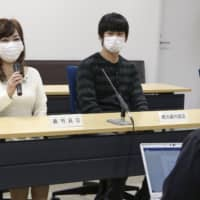 A lay judge (left) of a trial of a couple who were given prison sentences for confining their daughter for over 10 years speaks to reporters at the Osaka District Court on Thursday after the ruling was handed down. | KYODO