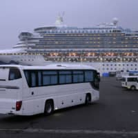 A coach travels toward the Diamond Princess cruise ship, docked in Yokohama on Feb. 16. | BLOOMBERG