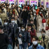 People wearing protective masks, following the COVID-19 outbreak, are seen at Shinjuku Station in Tokyo on Tuesday. | REUTERS
