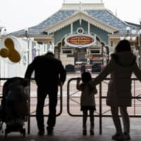 A family looks at the shuttered entrance of Tokyo Disneyland near Tokyo on Feb. 29 due to a closure in the wake of the coronavirus outbreak. | KYODO