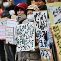 Protesters hold placards during a demonstration against nuclear energy, Prime Minister Shinzo Abe and the forthcoming Olympics Games, near the crippled Fukushima No. 1 nuclear power plant on Feb. 29, 2020. | AFP-JIJI