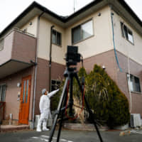 Yuji Onuma, an evacuee from the Fukushima town of Futaba, uses a tripod to take a selfie in front of his abandoned house in February. | REUTERS