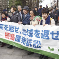 Plaintiffs and their supporters seek damages from the state and the operator of the Fukushima No. 1 nuclear power plant at Sendai High Court on Feb. 20. | KYODO