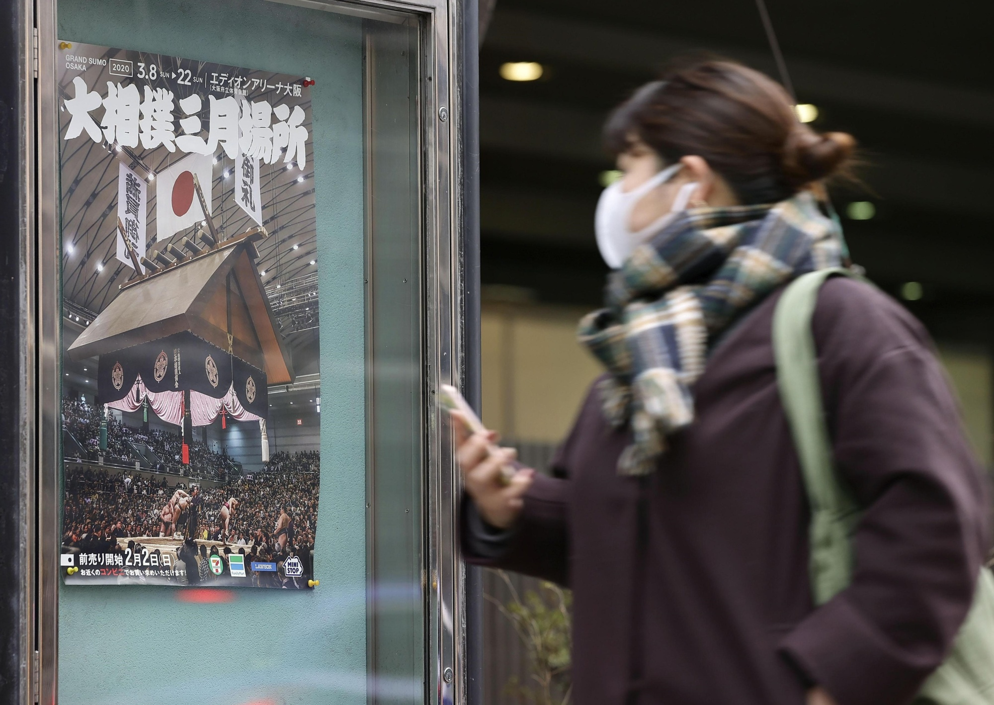 A woman looks at a poster for the Spring Sumo Tournament in Osaka on Sunday. The tournament will become another sports event to be held behind closed doors due to the coronavirus crisis spreading across the nation. | KYODO