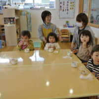 Children at the on-site nursery at Minato Suisan in Ishinomaki, Miyagi Prefecture, eat tarako rice balls. The company completed the day care facility in 2017 to help young female employees balance work and family. | KYODO