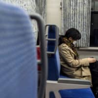 A passenger wearing a face mask travels on a train in Iwate Prefecture on Monday. | AFP-JIJI
