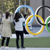 People take photographs of the Olympic rings at the Japan Olympic Museum in Tokyo. Organizers of the Tokyo Olympics have repeatedly stated that the games will go ahead on schedule despite the spread of the new virus that causes COVID-19. | BLOOMBERG