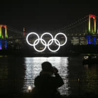 A photographer takes pictures of the illuminated Olympic rings in front of the Rainbow Bridge in Tokyo's Odaiba area on Jan. 24. | AP