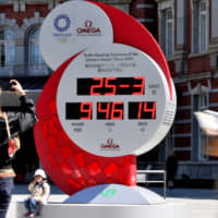 A countdown clock in front of Tokyo Station on Wednesday shows the current time instead of counting down to the Tokyo Olympics, a day after Prime Minister Shinzo Abe announced that the games will be postponed until next summer at the latest. | YOSHIAKI MIURA