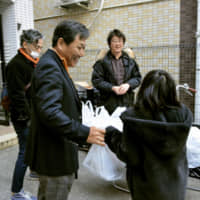 A representative (second left) of a nonprofit restaurant where children can eat for free in Osaka distributes a free lunch box to a child on March 5 amid the coronavirus outbreak. | KYODO