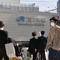 People walk in front of JR Sannomiya Station in Kobe on Friday, a day after the governors of Osaka and Hyogo prefectures requested that nonessential travel between them be avoided over the extended weekend. | KYODO
