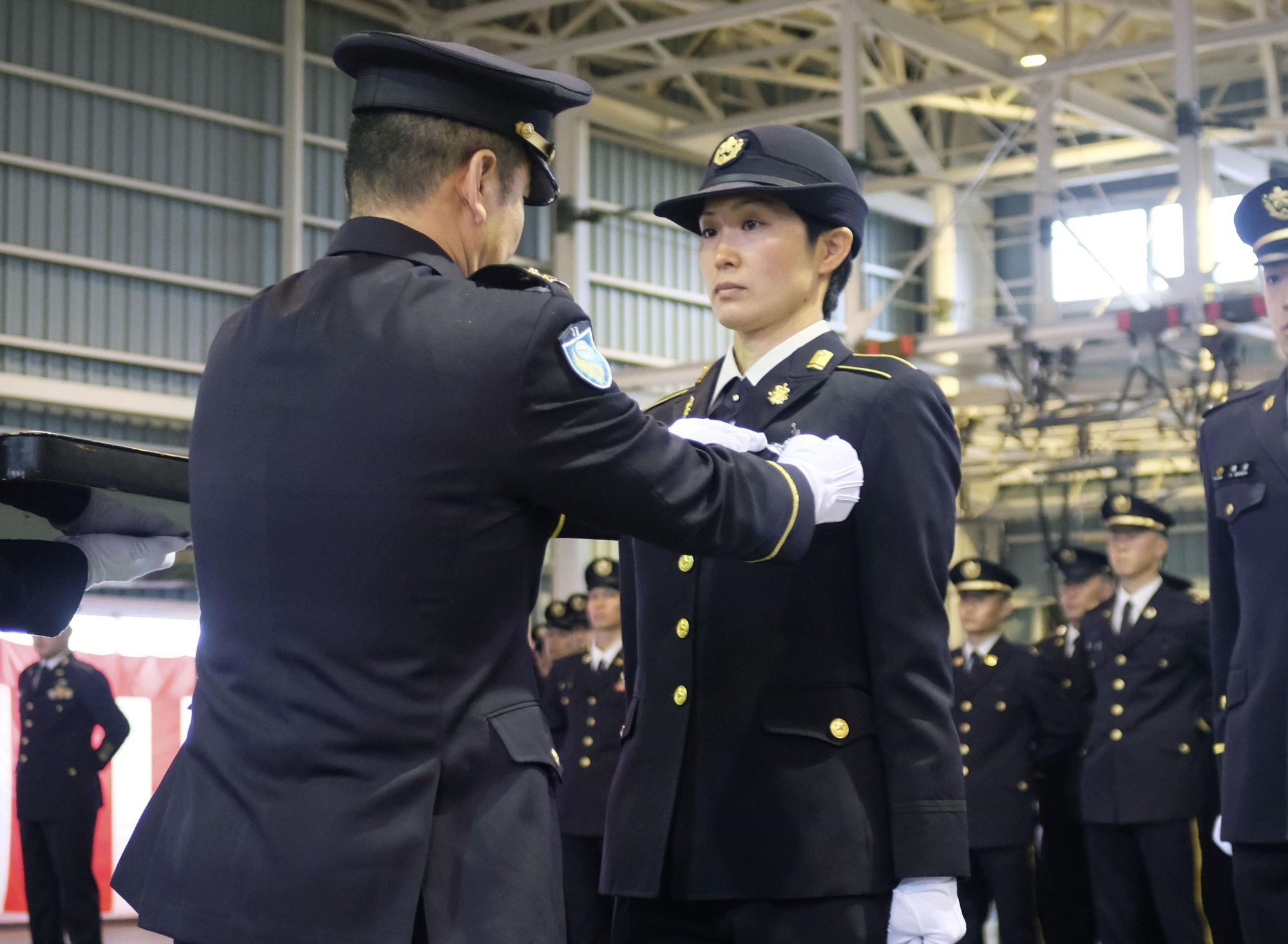 Sgt. Reina Hashiba is awarded the badge of an airborne brigade member at the Ground Self-Defense Force's Camp Narashino in Chiba Prefecture on Wednesday. | KYODO