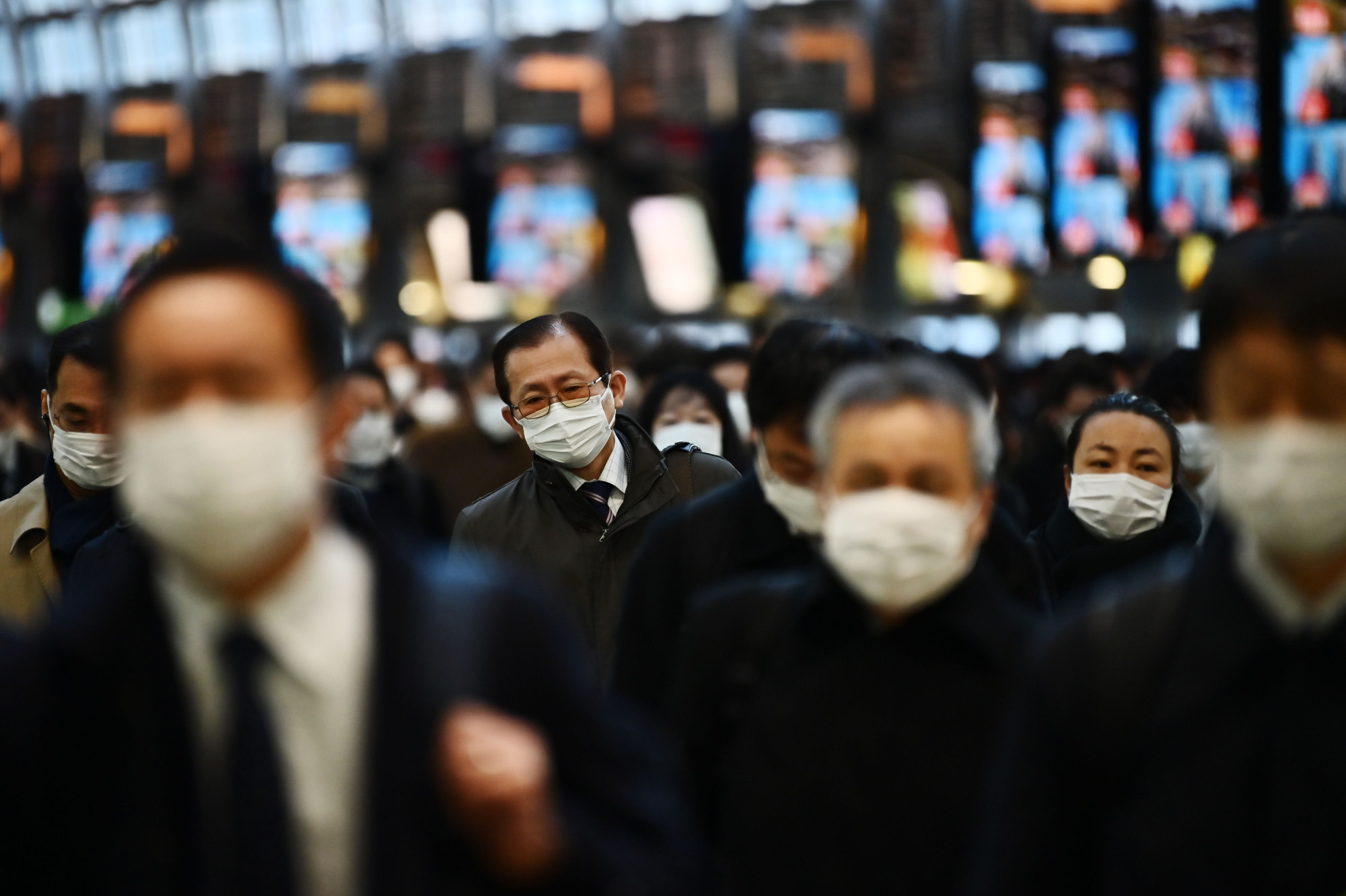 Mask-clad commuters make their way to work during morning rush hour at Shinagawa Station in Tokyo on Friday. | AFP-JIJI