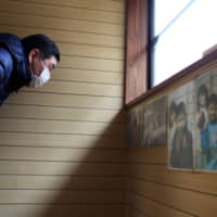Kazuo Ouchi, 62, father of young baseball player Ryoma Ouchi, looks at old photographs of his children at their now-abandoned house after their evacuation caused by the March 2011 earthquake, tsunami and nuclear disaster, in Iitate, Fukushima Prefecture. | REUTERS