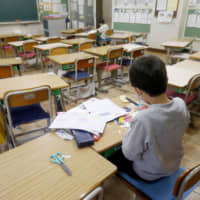 Two students study in an almost empty elementary school classroom in the city of Saitama on Monday. School closures began the same day, but some schools opened their doors for children whose parents were not at home. | KYODO