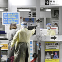 A quarantine officer in protective clothing directs those arriving from South Korea at Narita International Airport on Monday morning. | KYODO