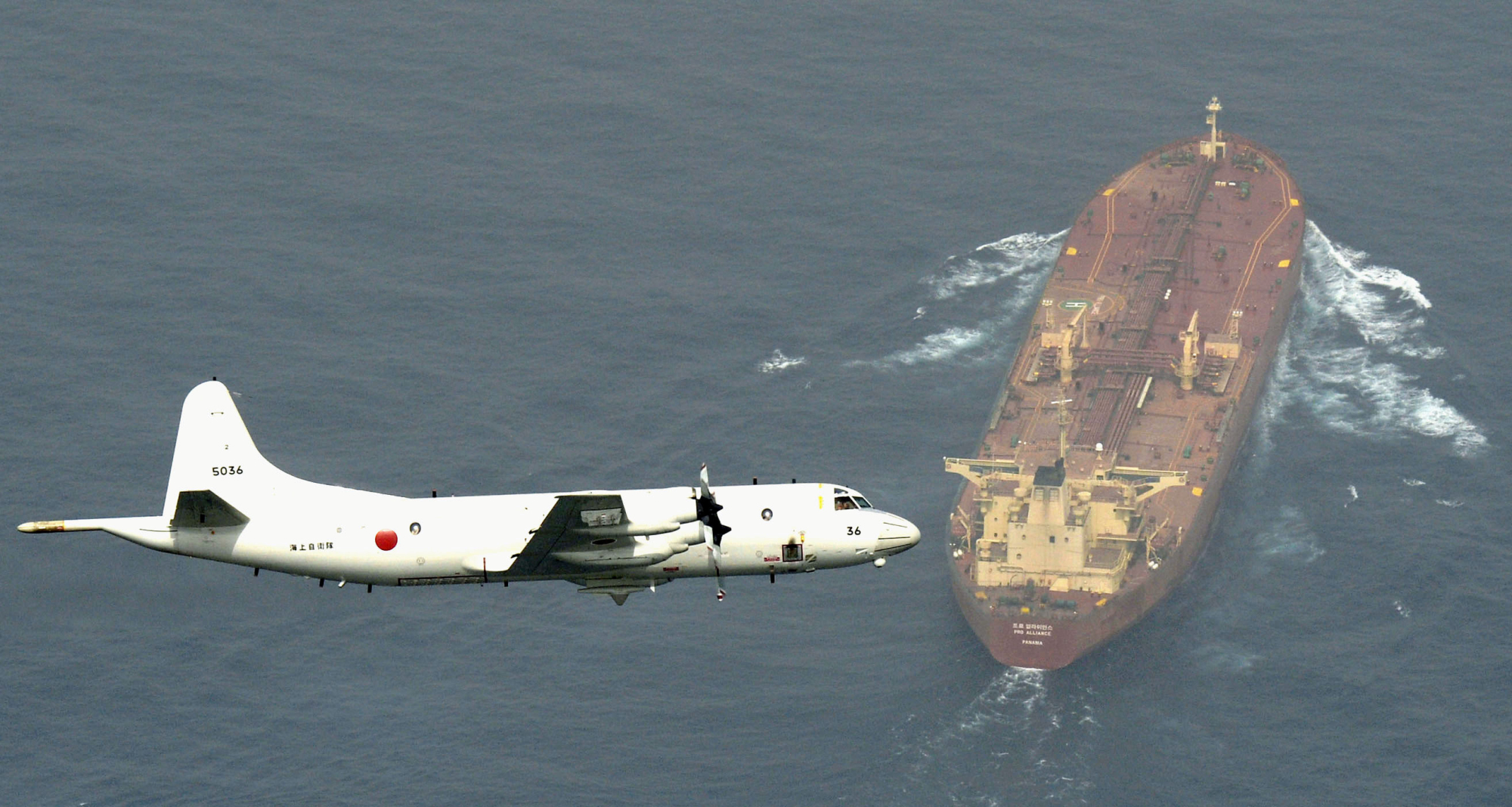 A Maritime Self-Defense Force P3-C Orion surveillance aircraft flies over an oil tanker during an anti-piracy operation in the Gulf of Aden, off Somalia, in August 2015.   KYODO
