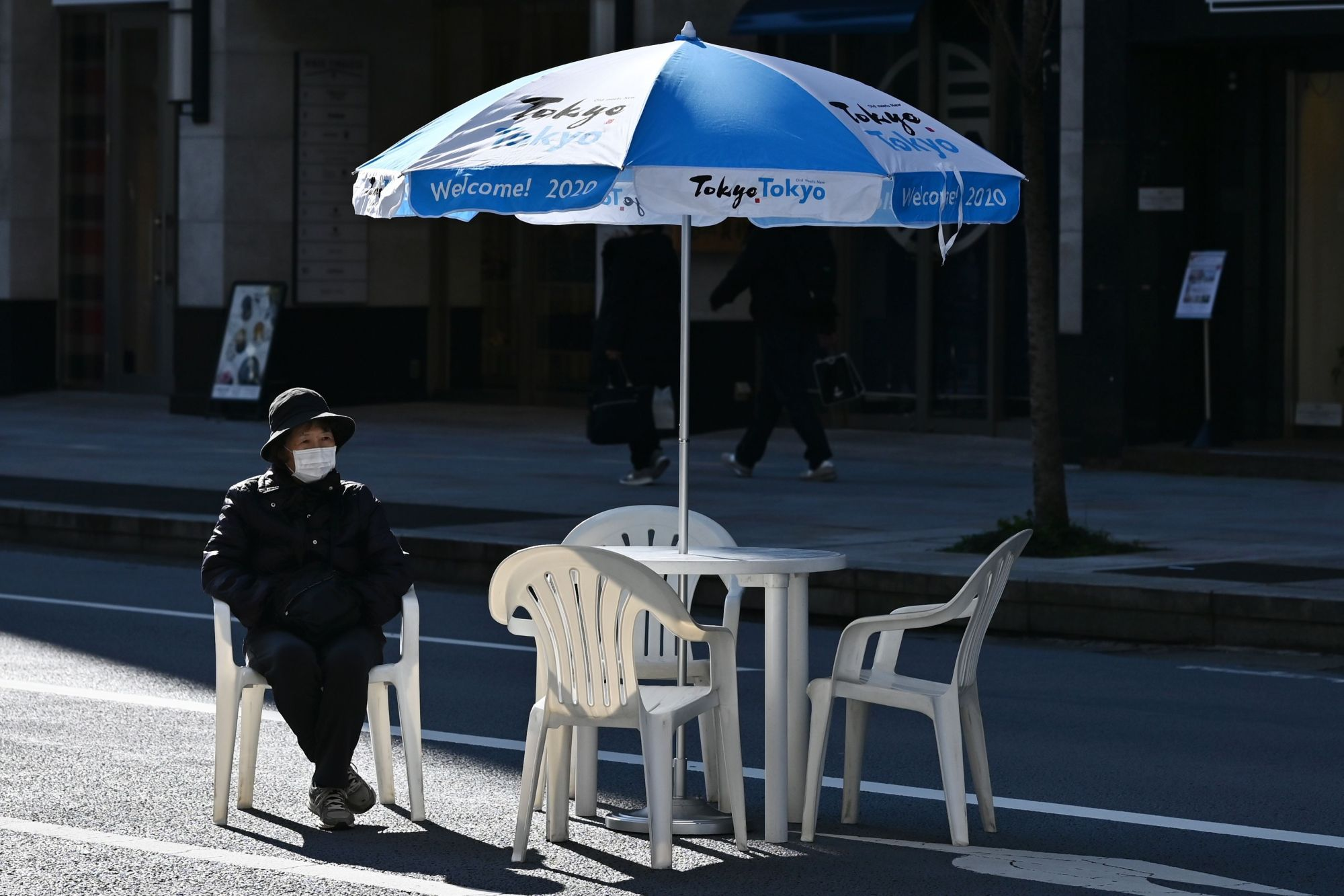 A woman sits alone in Tokyo's Ginza district on Sunday. | AFP-JIJI