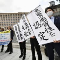 Plaintiffs and lawyers who filed a lawsuit seeking damages for having to evacuate after meltdowns at the Fukushima No. 1 nuclear power plant hold up banners Thursday in front of the Sendai High Court. | KYODO