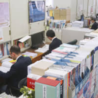 Education ministry officials in charge of screening textbooks continue their work at the ministry in March. | KYODO