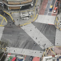 The famous scramble crossing in Shibuya is almost deserted on Saturday. | KYODO