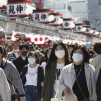Visitors wearing face masks walk through the Nakamise passage in Tokyo's Asakusa district on Friday. | KYODO