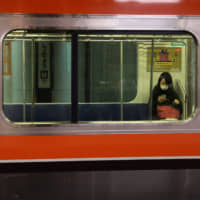 A woman with a mask sits in a train at Tokyo Station on Tuesday. | REUTERS