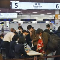 Travelers from international flights line up at a quarantine counter at Tokyo's Haneda Airport on Wednesday. | KYODO
