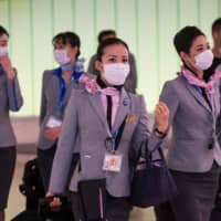 Flight crew from Japanese airline ANA wear face masks to protect against the spread of the COVID-19 new coronavirus as they arrive at Los Angeles International Airport on Saturday. | AFP-JIJI