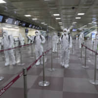 South Korean soldiers wearing protective suits spray disinfectant to prevent the spread of the new coronavirus at Daegu International Airport on Friday. Seoul expressed 'extreme regret' Friday over Japan's request that people arriving from South Korea and China undergo 14-day quarantines due to a surge in viral infections. | AP