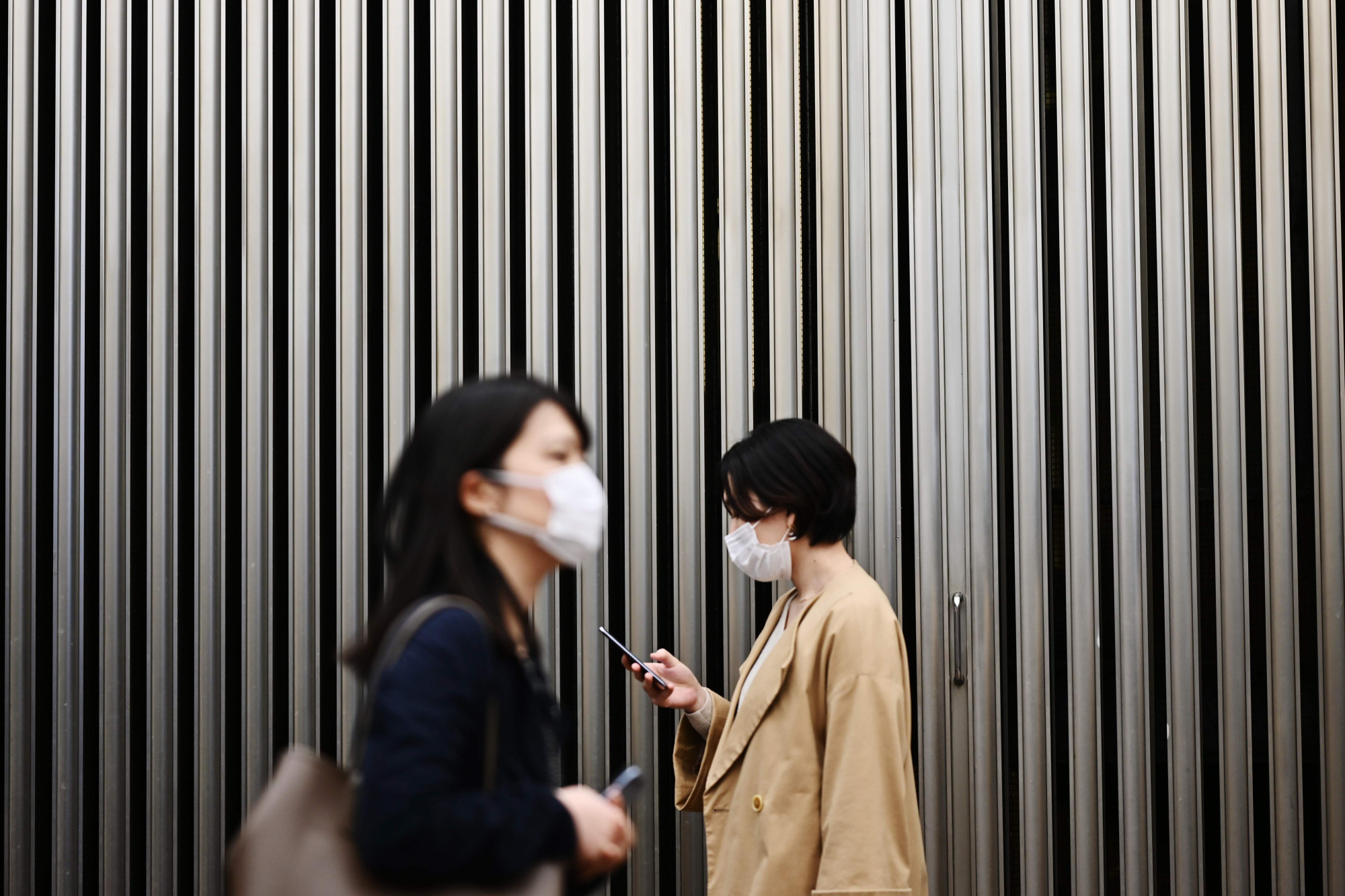 People wear face masks amid concerns over COVID-19 in Tokyo's Yurakucho district on Wednesday. Health experts have been puzzled as to why Japan is still seeing a relatively low number of infections from the deadly virus outbreak so far. | AFP-JIJI