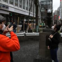 A woman wearing a protective face mask amid an outbreak of COVID-19 poses for a picture next to a similarly mask-clad statue of Hachiko in front of Tokyo's Shibuya Station on Sunday. | REUTERS